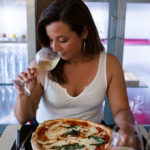 Katie Parla sniffing wine and enjoying pizza