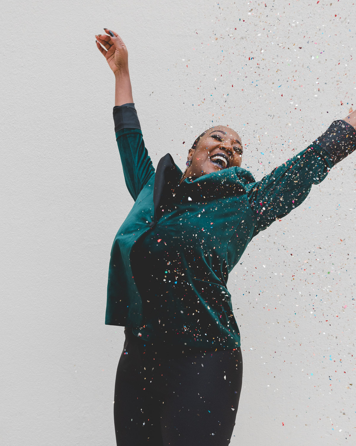 Woman looking happy, jumping up with her arms up in the air and confetti raining down