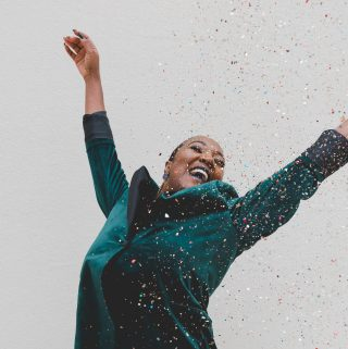 Woman jumping up looking happy with confetti raining down - square